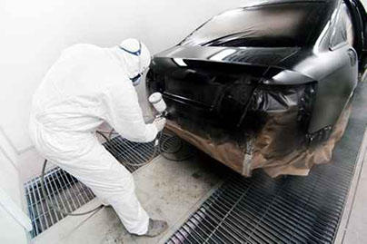 a picture of a man spraying a black car
